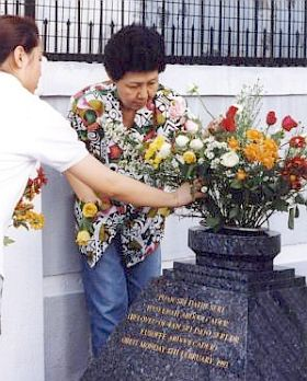 Saying goodbye: Haseenah's granddaughter Christina (left) and daughter Julie placing flowers on her grave on the third anniversary of her death.