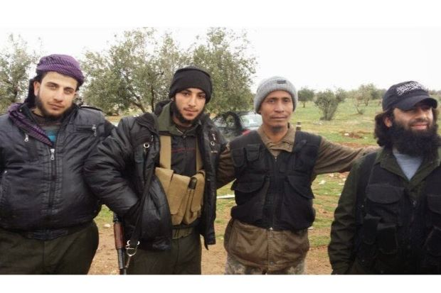 Brothers in arms: Lotfi (second right) posing with unidentified mujahideen fighters.