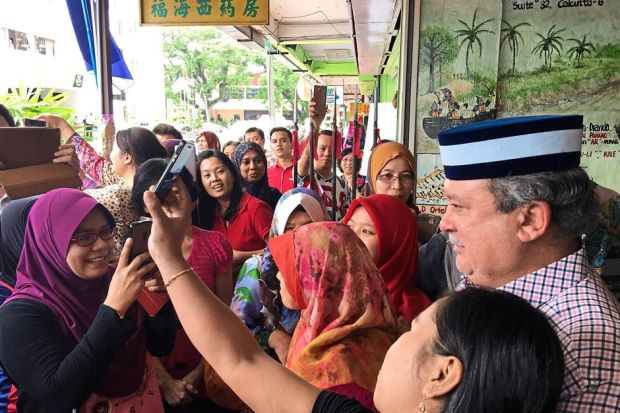 Sultan Ibrahim posing for a wefie with members of the public.