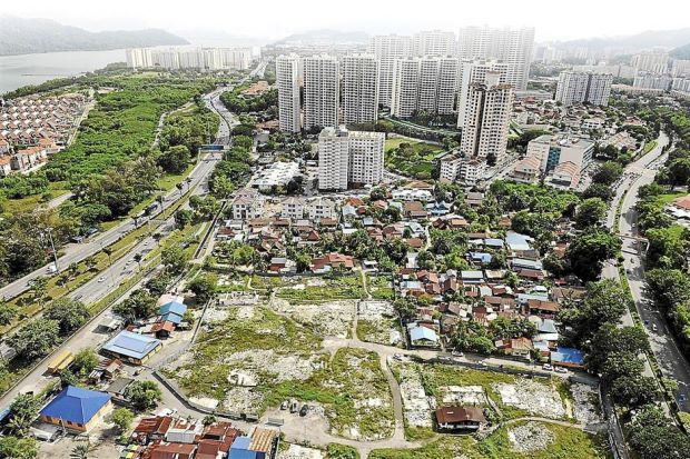 Changing landscape: The original Kampung Batu Uban is overshadowed by new condominiums and apartments being built in the area.