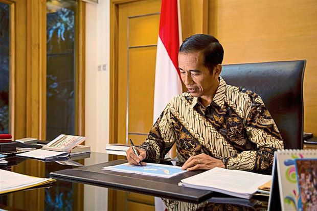 Ready to serve: Jokowi going through documents at his office in Jakarta. - AFP